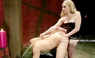 Blonde dominatrix dressed in latex paddles and fucks in the ass with a strapon a man