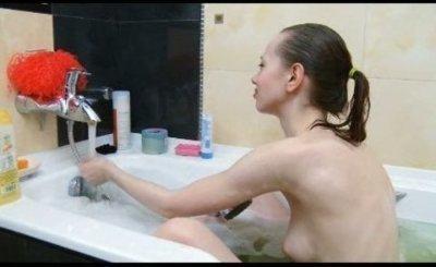 Thin teenager washing body in the bath tube